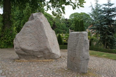 "Jelling runestones. To the left is ""Denmark's birth certificate,"" on the right Gorm's memory stone for his wife, Thyra."